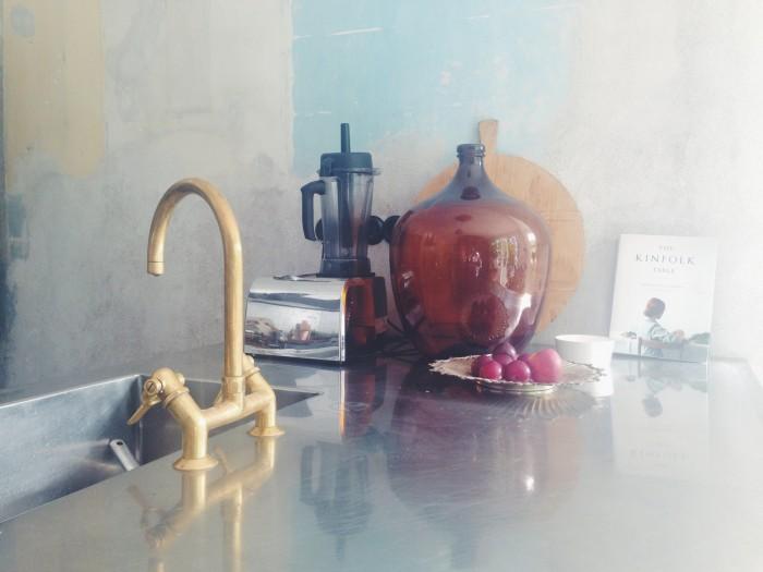 hemma hos malin persson kök köksbänk blandare kran i mässing glasflaskor patinerad vägg